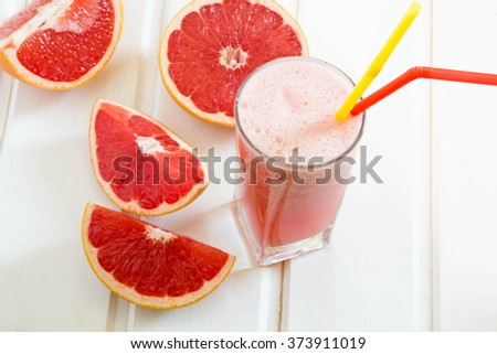 Grapefruit juice and ripe grapefruits on a wooden background - stock photo