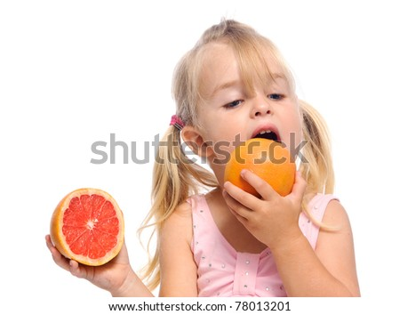 grapefruit lick by a young blonde girl, isolated on white in studio