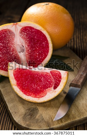 Grapefruit (sliced) on vintage wooden background (close-up shot)