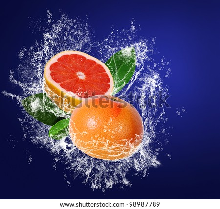 Grapefruits with leaves in water drops on the dark blue background - stock photo