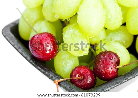 grapes and cherry in the bowl  isolated on white