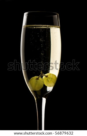 Grapes floating in champagne glass with black background