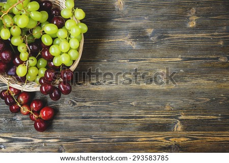 Grapes in a wicker basket on a wooden background