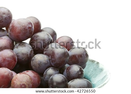 Grapes on a blue bowl, isolated on white.