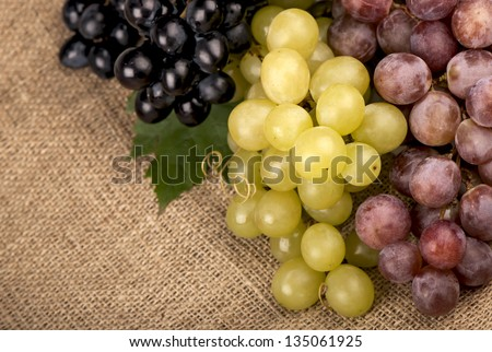 Grapes on a old linen fabric background texture - stock photo