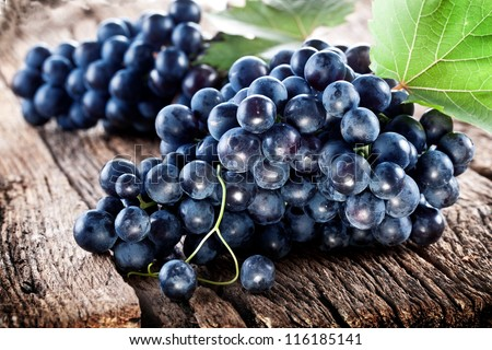 Grapes on a old wooden table. Blue grape.