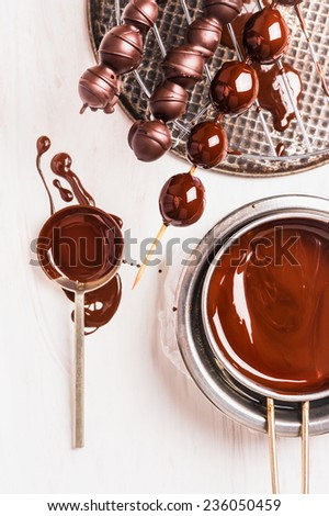 Grapes on brochette and liquid chocolate on white wooden background - stock photo