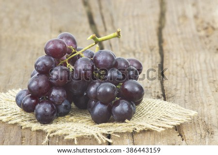 grapes on old wooden background - stock photo