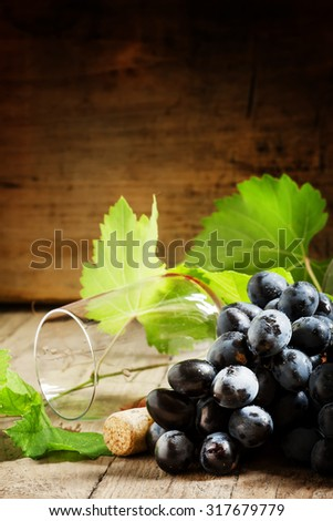 Grapes with vine and wine glass on a wooden background, selective focus - stock photo