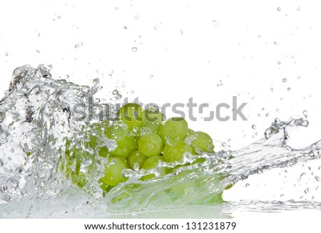 Grapes with water splash over white - stock photo
