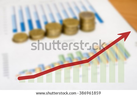 Graph and money coins with arrow on the table - stock photo