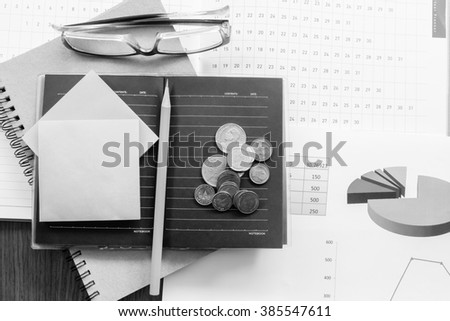 graph and money on the wooden table with black and white color concept - stock photo