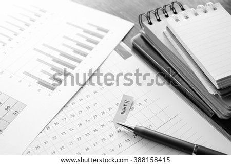 graph and note book on the wooden table with black and white color concept - stock photo
