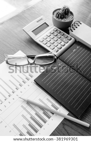 graph and note book on the wooden table with black and white concept - stock photo
