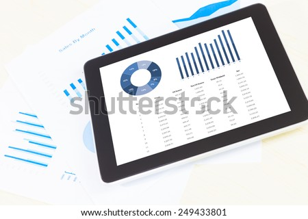 graph display in digital tablet and paper, pen,smartphone. Above view shot. - stock photo