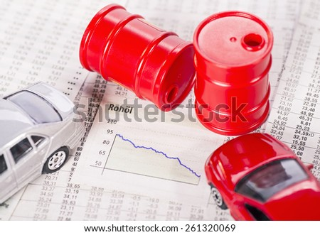 Graph with a falling curve surrounded by cars and oil barrels. - stock photo