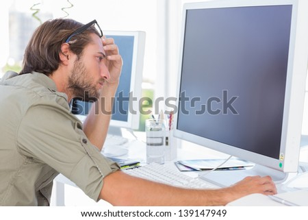 Graphic artist looking at his screen sitting at his desk - stock photo