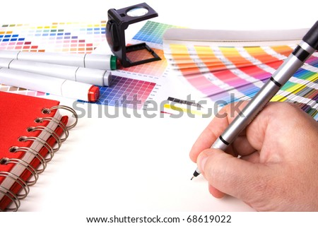 graphic design and coloured swatches and pens on a desk - stock photo