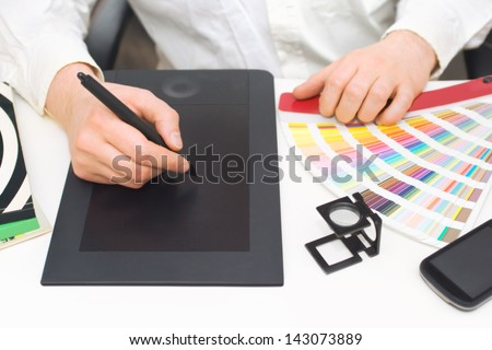 Graphic design, printing, advertising Graphic designer working with digitizer, magnifier, pantone palette, smart phone, magazines on desk - stock photo