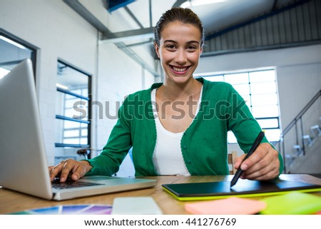 Graphic designer drawing on a graphic tablet while using laptop in office - stock photo