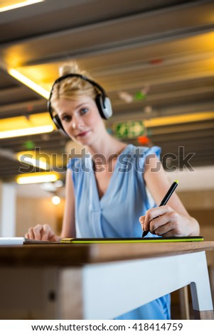 Graphic designer listening to headphones while using graphic tablet in office - stock photo