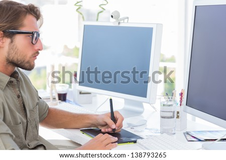 Graphic designer using graphics tablet to do his work at desk - stock photo