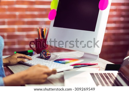 Graphic designer working at desk against red brick background - stock photo