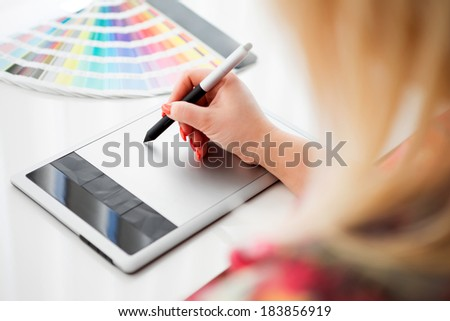 Graphic designer working on a digital tablet in the background with palette - stock photo