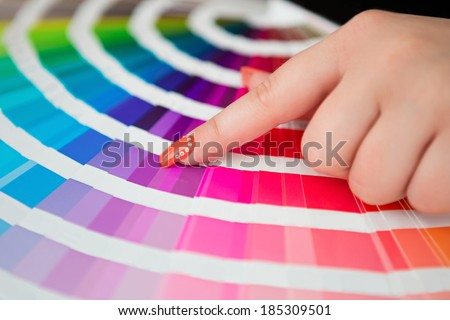 Graphic designer working with cmyk palette in studio - stock photo
