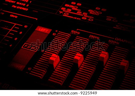 graphic equalizer close up in red tones and with dramatic light - stock photo