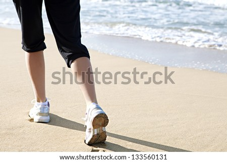 Graphic low section view of a young woman's legs and feet running along the sea shore exercising, wearing sport trainers. Rear view.