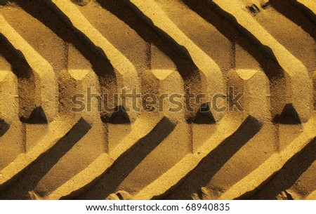 Graphic photo of a wide tire track in golden sand - stock photo