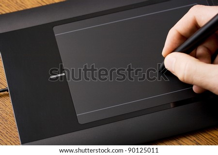 Graphic tablet on wooden table with hand and pen in it - stock photo