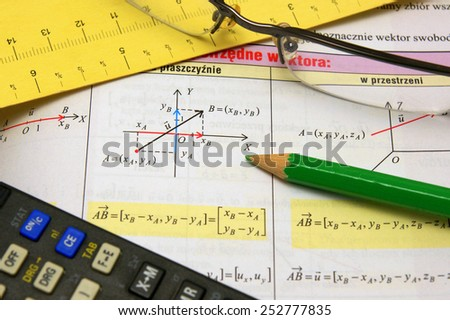 Graphs and charts of vectors (vector) theory together with glasses, calculator and green pencil - stock photo