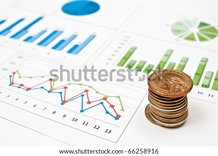 Graphs and charts with stacks of coins - stock photo