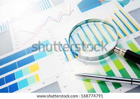 Graphs, magnifier and pen. Analyzing finances.  - stock photo