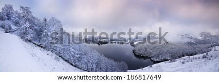 Grasmere Lake and village in the English Lake District seen from Loughrigg Terrace in heavy snow - stock photo