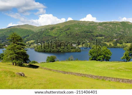 Grasmere Lake District Cumbria England UK with blue sky mountains and white clouds on a beautiful summer day in this National Park