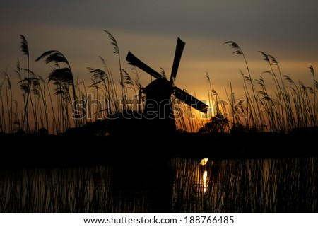 Grass and Dutch windmill at sunset at Kinderdijk in Netherlands - stock photo