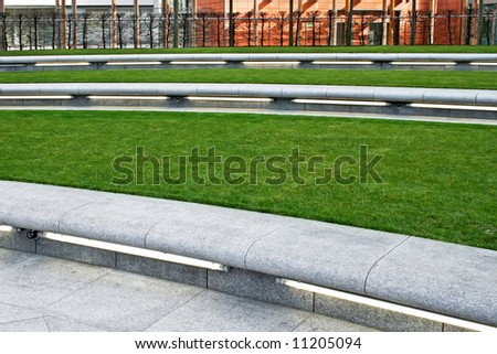 Grass area in park with concrete bench