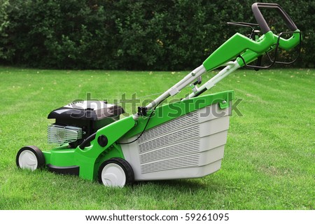 grass cutter on a green meadow - stock photo