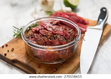 Grass Fed Flank Steak Sliced and Mixed with Marinade to Make Beef Jerky - stock photo