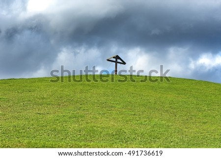 Grass field background and dramatic cloudy sky with wooden christ cross silhouette on top of grassland hill detail exterior nature scene theme landscape view