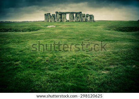 Grass field leading to Stonehenge on a cloudy gray day - stock photo