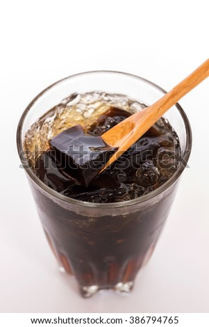 Grass jelly; dessert herbal gelatin with syrup, ice, and brown sugar in vintage glass