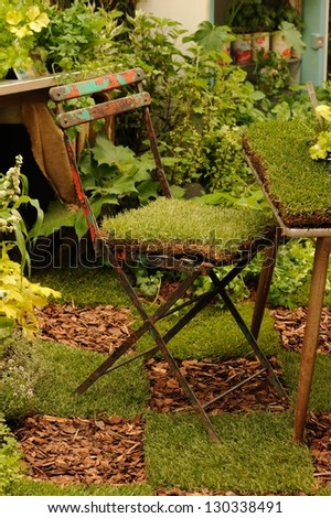 Grass on old iron chair - stock photo