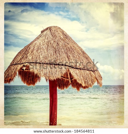 Grass palapa umbrella on beach, instagram style - stock photo