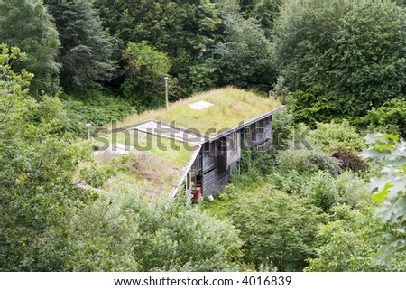 grass roofs and solar panels on Welsh eco cabins - stock photo