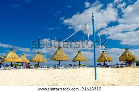 Grass umbrellas at a beach with volleyball net in the middle - stock photo