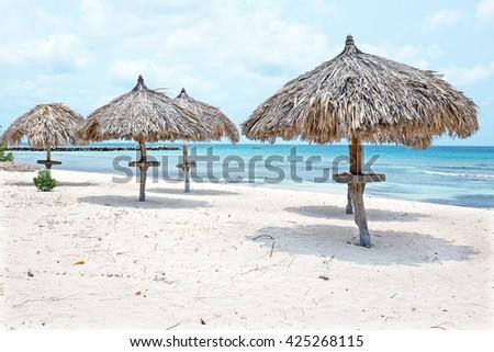 Grass umbrellas at the beach on Aruba island  - stock photo